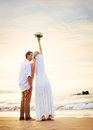 Bride and groom beautiful tropical beach at sunset romantic ma watching on married couple Stock Images