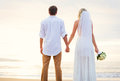 Bride and groom beautiful tropical beach at sunset romantic ma watching on married couple Stock Photo