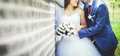 Bride and groom in a blue suit embracing near a white brick wall Royalty Free Stock Photo