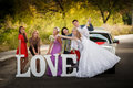 Bride and groom and bride s girlfriends on the road happy Royalty Free Stock Images