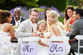 Bride and groom with bridesmaid at wedding reception sitting on chair outdoors smiling to camera Stock Images