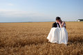 Bride and groom carrying her in the wheat field trash the dress Stock Photography