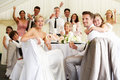 Bride and groom celebrating with guests at reception smiling to camera Royalty Free Stock Images