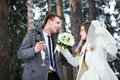 Bride and groom with champagne glasses in winter forest wedding day Stock Photography