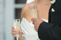 Bride and groom with champagne in white in black holding glasses of Royalty Free Stock Photography