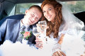 Bride and groom clinking glasses in limousine smiling Royalty Free Stock Images