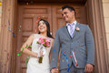 Bride and groom with confetti happy outside a church in the air Royalty Free Stock Photo
