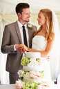 Bride and groom cutting wedding cake at reception smiling to each other Stock Images