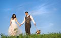 Bride and groom with dog walk their beagle in the green field Royalty Free Stock Photos