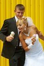 The bride and groom eat ice cream funny yellow background Royalty Free Stock Photos