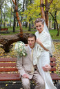 Bride and groom embrace at bench in autumn park Stock Photo