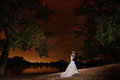 Bride and groom embracing by the lake under the stars. Royalty Free Stock Photo