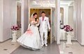 Bride and groom emerge from the doors of the Palace of weddings Stock Photo