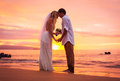 Bride and groom enjoying amazing sunset on a beautiful tropical beach romantic married couple holding hands Royalty Free Stock Photos