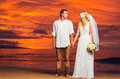 Bride and groom enjoying amazing sunset on a beautiful tropical beach romantic married couple holding hands Stock Photo