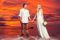 Bride and groom enjoying amazing sunset on a beautiful tropical beach romantic married couple holding hands Stock Images
