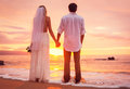 Bride and groom enjoying amazing sunset on a beautiful tropical beach romantic married couple holding hands just married Royalty Free Stock Photos
