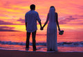 Bride and groom enjoying amazing sunset on a beautiful tropical beach romantic married couple holding hands memoire Royalty Free Stock Photos