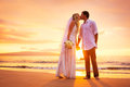 Bride and groom enjoying amazing sunset on a beautiful tropical beach romantic married couple kissing Stock Images