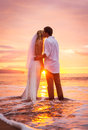 Bride and groom enjoying amazing sunset on a beautiful tropical beach romantic married couple kissing Stock Photo