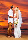 Bride and groom enjoying amazing sunset on a beautiful tropical beach romantic married couple kissing sexy scene Stock Photography