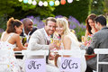 Bride and groom enjoying meal at wedding reception looking to camera smiling Stock Photos
