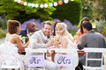 Bride and groom enjoying meal at wedding reception outdoors sitting down looking to camera smiling Royalty Free Stock Image