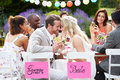 Bride and groom enjoying meal at wedding reception outdoors smiling to each other with heads touching Royalty Free Stock Images
