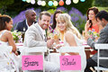 Bride and groom enjoying meal at wedding reception smiling camera Royalty Free Stock Image