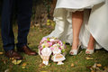 Bride and groom feet with wedding bouquet and wedding gingerbrea