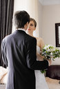 Bride and groom with flowers in a room looking each other Stock Photo