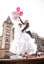 Bride and groom flying on helium balloons in the city young Royalty Free Stock Photos