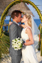 Bride and groom getting married in beach ceremony kissing Royalty Free Stock Images