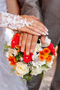 Bride and groom hands of the the with wedding rings on the bouquet Stock Image