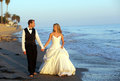 Bride and groom happy wedding couple walking on the beach Stock Photo