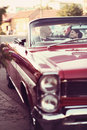 The bride and groom have fun behind the wheel of red retro vintage car. Wedding. Royalty Free Stock Photo
