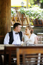 Bride and groom having fun at cafe outdoor Stock Photos