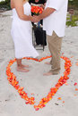 Bride and Groom in heart on sand Royalty Free Stock Photo