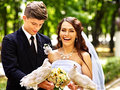 Bride and groom holding dove outdoor in park Stock Photo