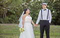 Bride and groom a holding hands in a park setting Royalty Free Stock Photos