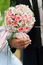 Bride and groom holding hands with rings on floral bouquet Royalty Free Stock Photography