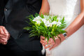 Bride with groom holding a wedding bouquet at ceremony Stock Images