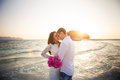 Bride and groom hug at spit at sunrise barefoot in shallow water against Stock Photography
