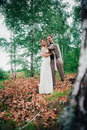 Bride and groom hugging on the background of leaves forest Royalty Free Stock Photo