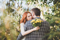 The bride and groom hugging each other in the forest with yellow flowers bouquet Stock Image