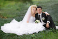 Bride and groom hugging and looking in the eyes of one another sitting at a green grass Royalty Free Stock Photo