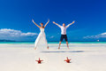 Bride and groom jumping on tropical beach shore with two red sta having fun starfish in the sand Stock Images
