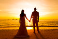The bride and groom are kept hands on a tropical beach silhoue silhouette photo at sunset Stock Photo