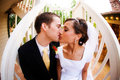 Bride and groom kiss on stairwell Stock Photo