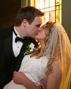 Bride and groom kissing at the altar Stock Photos